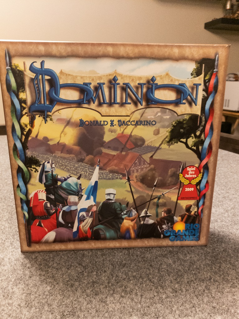 Image is of Dominion Game Box sitting on a table