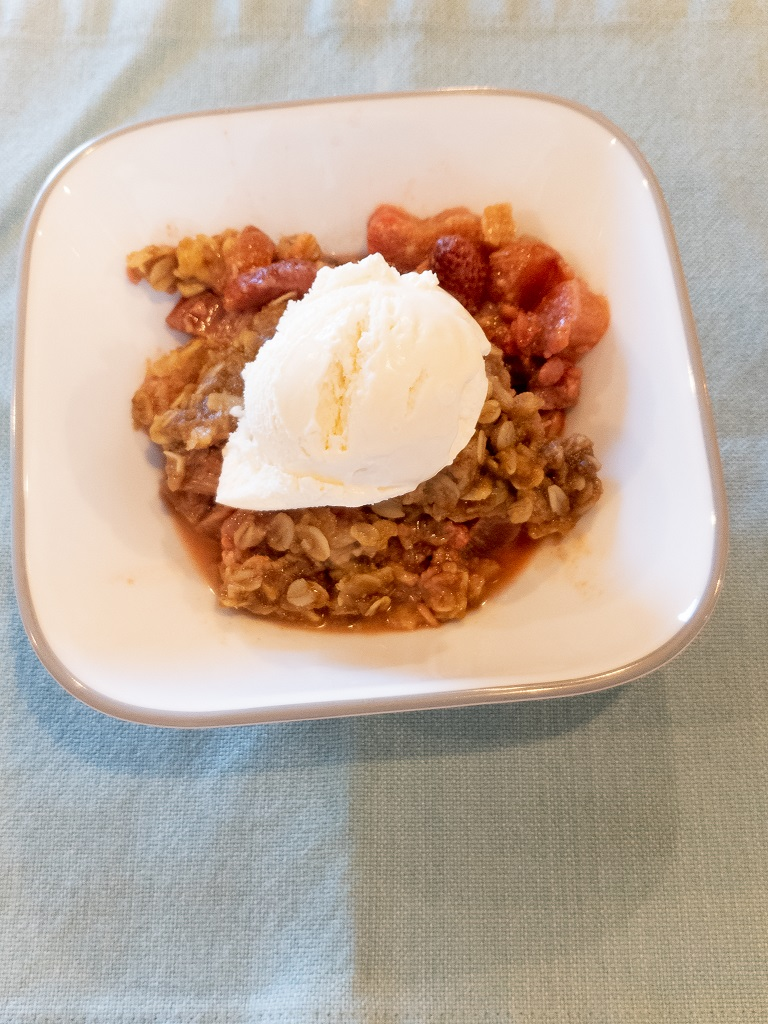Dish of Rhubarb Crips with a scoop of Vanilla ice cream on top