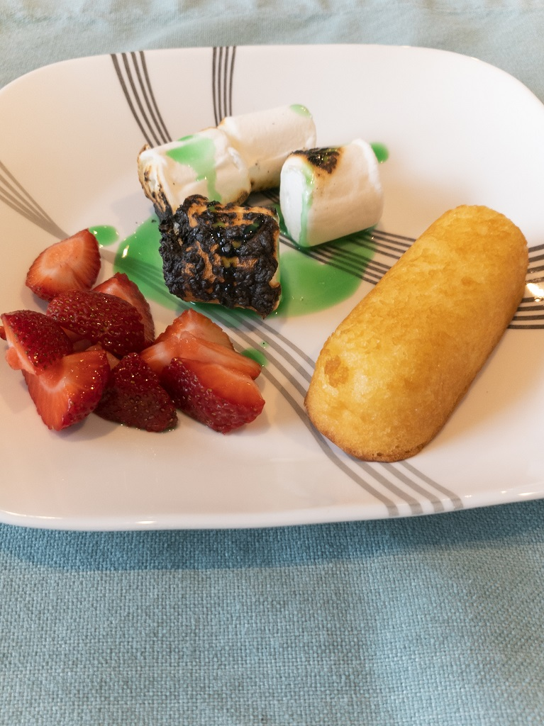 Image is of Twinkies, roasted marshmallows, and strawberries