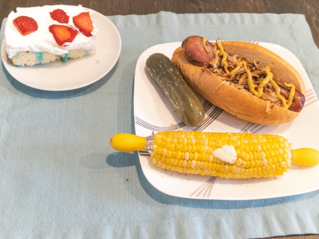 Image is of Jell-O poke cake, brat on bun, corn on the cob, and a pickle