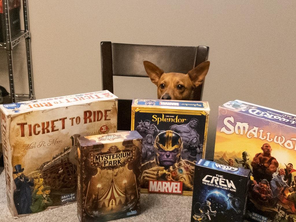 Image of dog peeking above the 5 game boxes