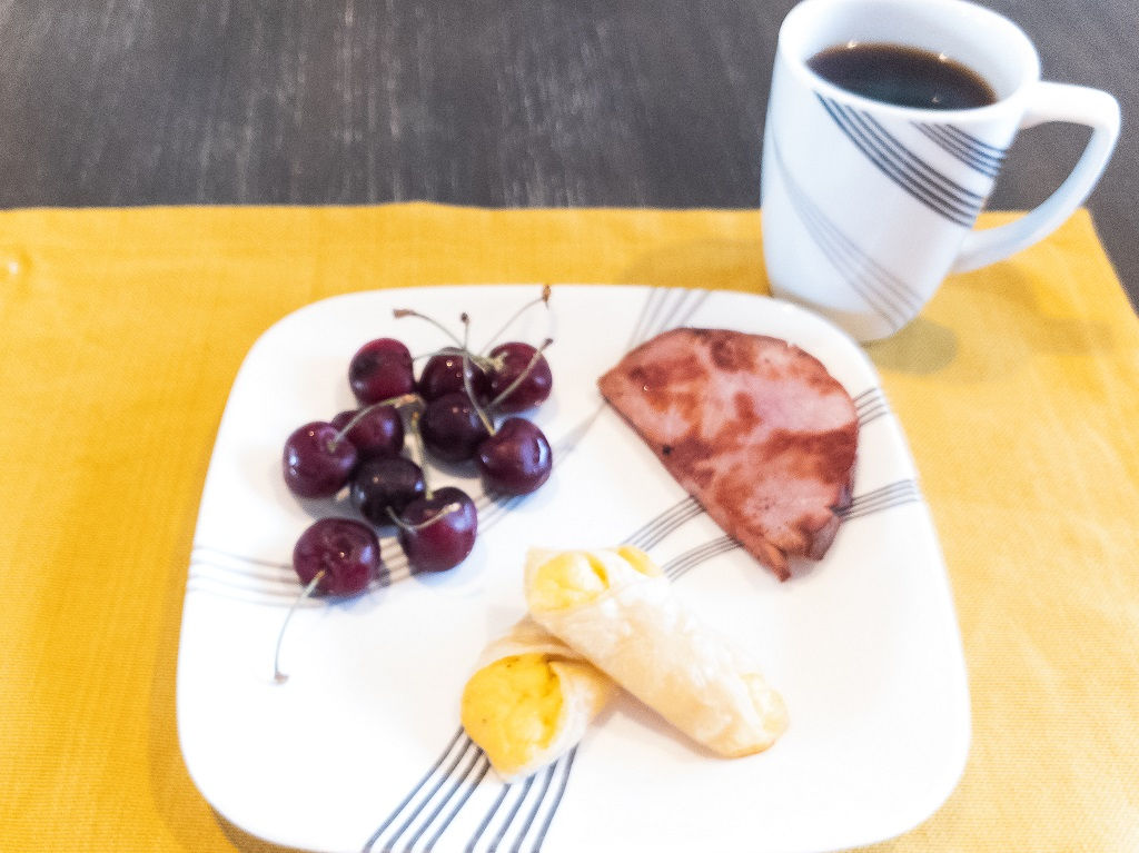 Image of brunch: cheese turnovers, ham slice, fresh cherries, and coffee